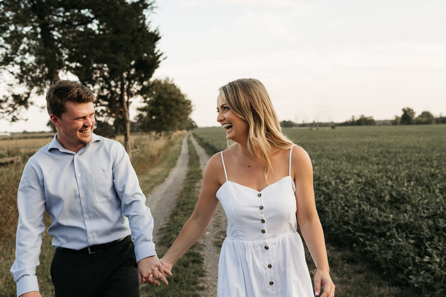 engaged couple holding hands walking at sunset at the farm