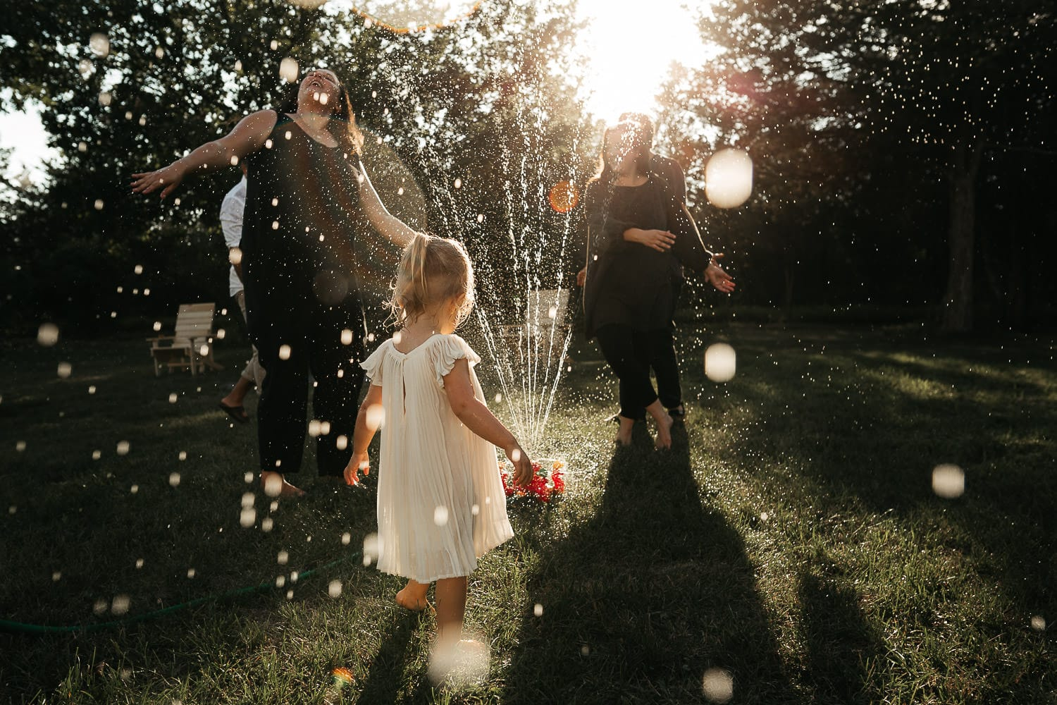 toddler in white dress dancing with mom and aunt in the sprinkler at sunset in pec