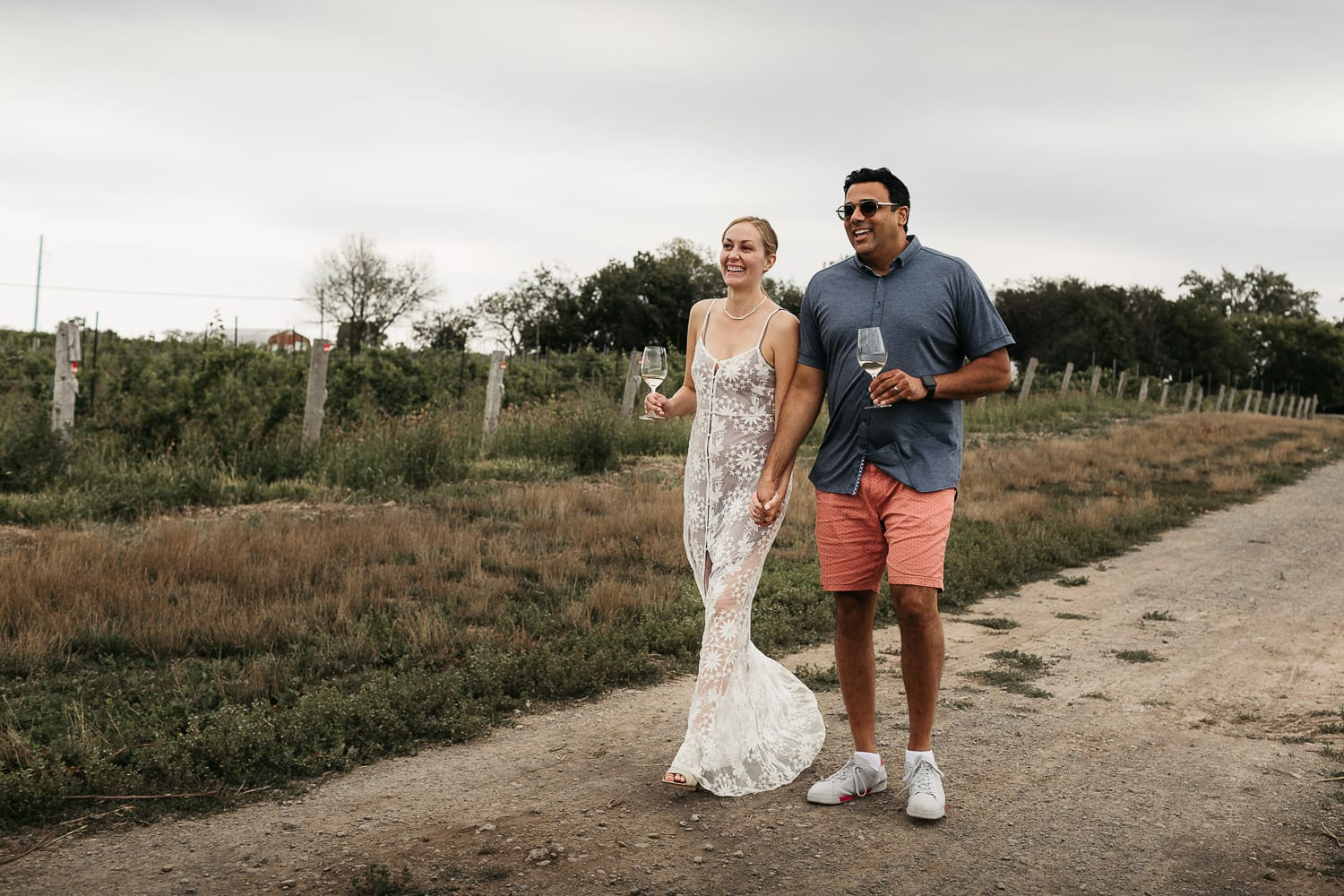 bride and groom walking down lane at Carlo estates winery in prince Edward county