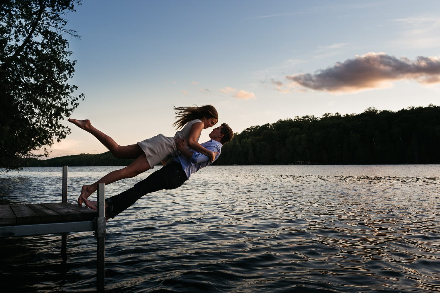 engaged couple trust fall off the dock into the lake